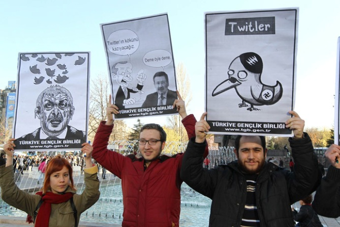 People in Turkey hold placards as they protest against Turkey's Prime Minister after the government of Turkey blocked access to Microblogging platformTwitter